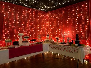 Wedding Desert table at Red River Event Center. 2 Tables with string lights and red fabric in the background