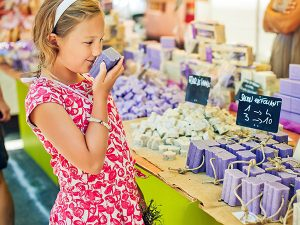 girl smelling a bar of soap at a craft fair