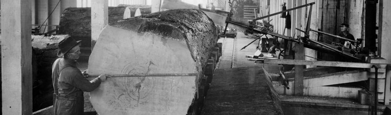 Historical black and white photo of a log on a saw mill at Red River Liquor Co.'s location